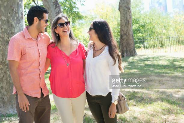 Smiling mother laughing with son and daughter in park