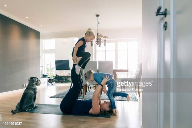 smiling mother lifting happy daughters while lying on exercise mat at home - vitaliteit stockfoto's en -beelden