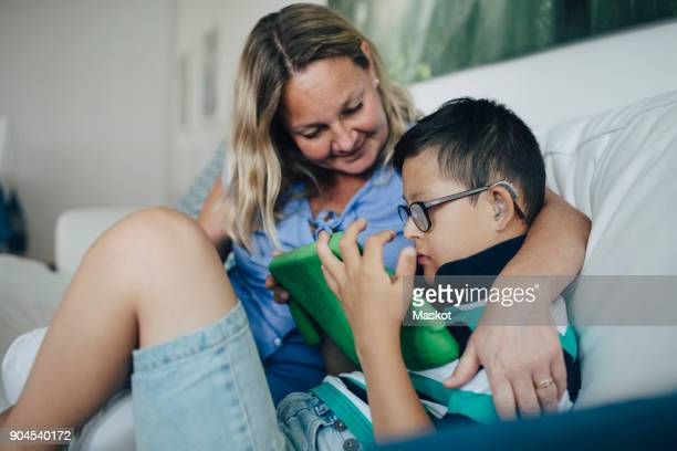 Smiling mother looking at disabled son using digital tablet while sitting on sofa