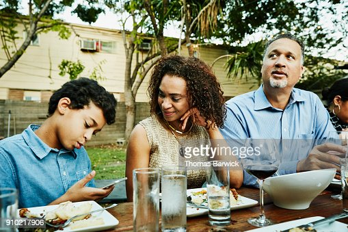 Smiling mother looking at son playing on smartphone during outdoor family dinner