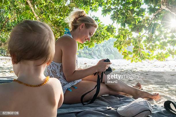 Smiling mother looking at summer vacation photos on digital camera.