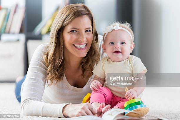 Smiling mother or nanny with baby girl