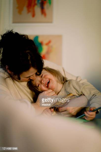 smiling mother playing with disabled daughter at home - intellectually disabled stock pictures, royalty-free photos & images