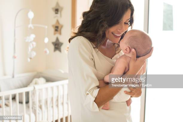 smiling mother playing with son at home - mother stock pictures, royalty-free photos & images