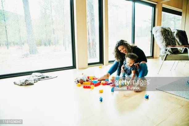 Smiling mother playing with toddler daughter on floor on living room