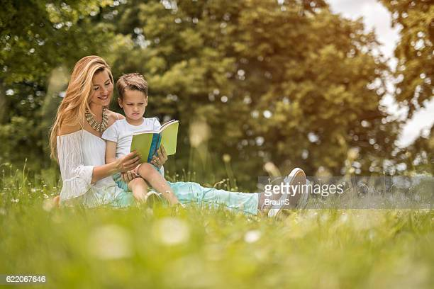 Smiling mother reading a book to her son in nature.