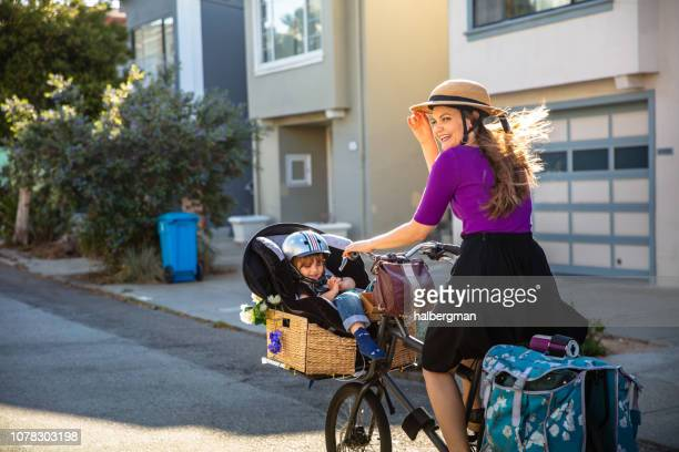 Smiling Mother Riding Cargo Bike on Sunny Day with Kid in Basket