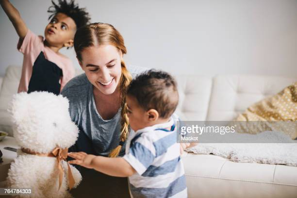 smiling mother showing teddy bear to toddler while boy playing by sofa at home - mama bear stock photos and pictures