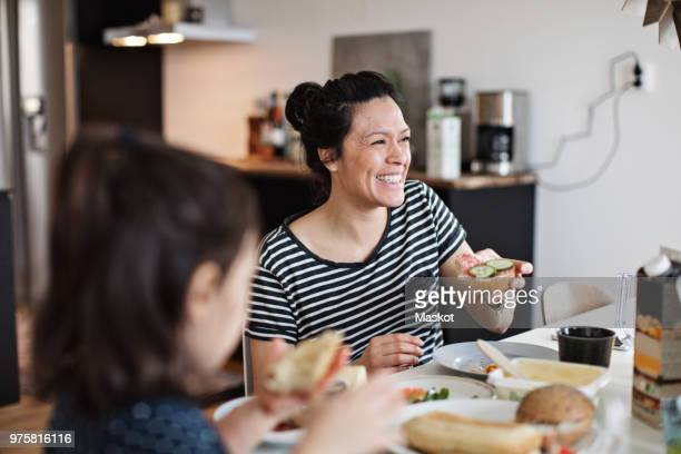 smiling mother sitting with daughter while having breakfast at dining table - eating stock pictures, royalty-free photos & images