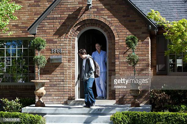 Smiling Mother stands at front door of house as son departs