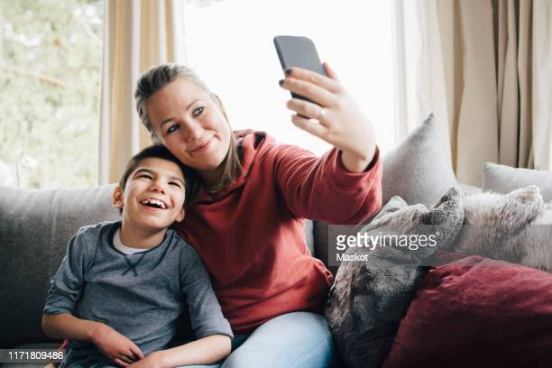 smiling mother taking selfie with autistic son while sitting on sofa at home - differing abilities fotografías e imágenes de stock
