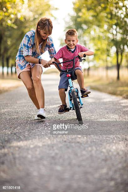 Smiling mother teaching her son to ride bicycle in nature.