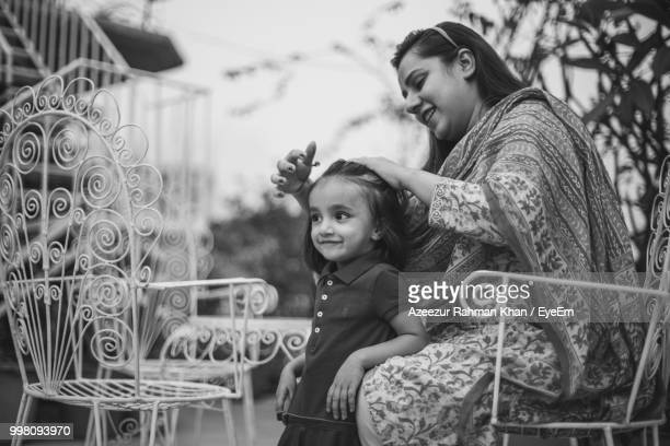 smiling mother tying daughter hair - bangladesh mother stock pictures, royalty-free photos & images