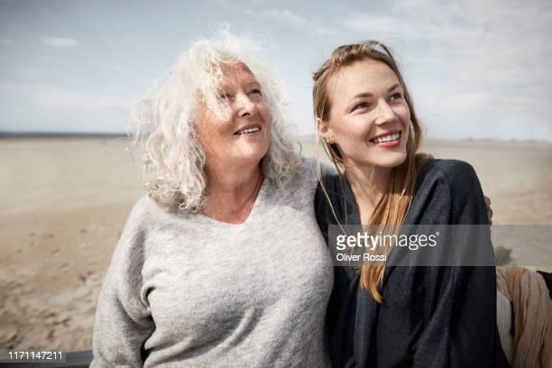 smiling mother with adult daughter on the beach looking sideways - sleeswijk holstein stockfoto's en -beelden