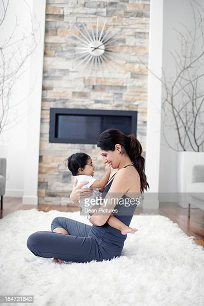 smiling mother with baby girl (6-11 months) in living room - 6 11 months stock pictures, royalty-free photos & images