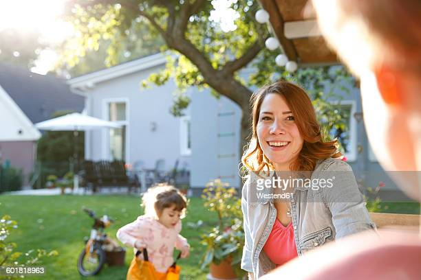 Smiling mother with daughter in garden