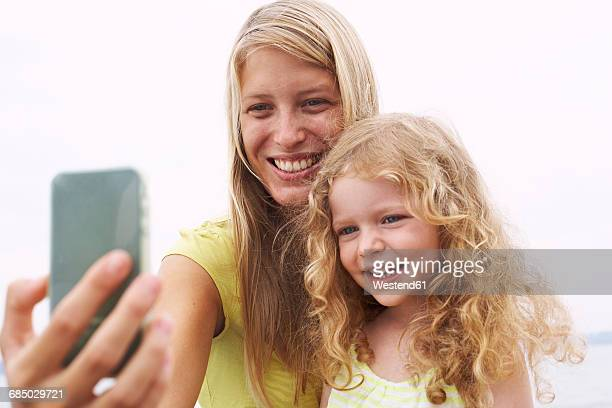Smiling mother with daughter taking a selfie