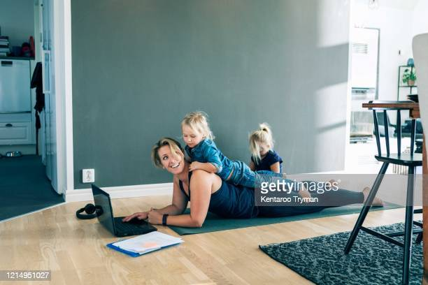 smiling mother with laptop looking at daughter lying on her back while girl sitting in living room at home - working from home stock pictures, royalty-free photos & images