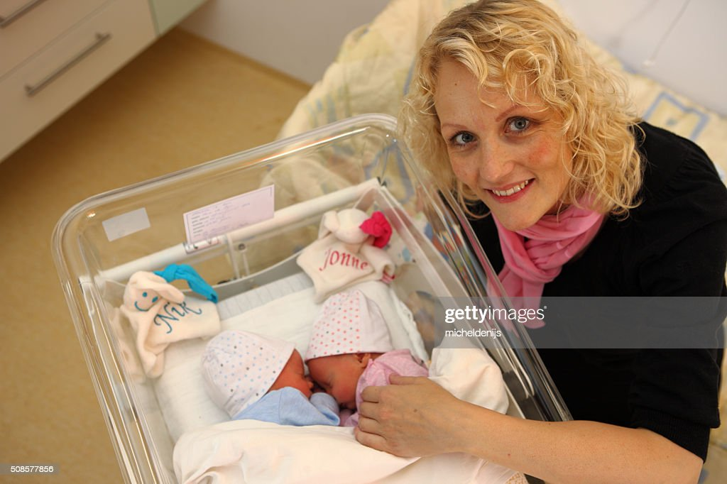 Smiling Mother With Newborn Twins In Hospital : Stockfoto