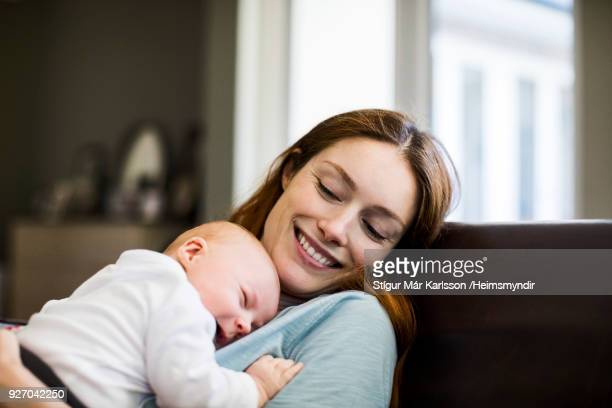 Smiling mother with sleeping newborn son on sofa