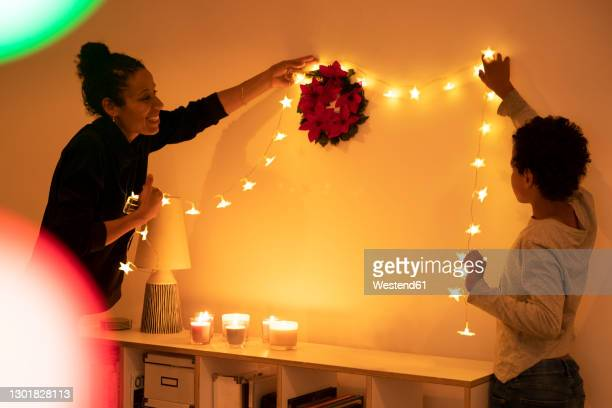 smiling mother with son decorating illuminated christmas lights on wall at home - decoration stock pictures, royalty-free photos & images