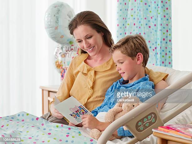 Smiling mother with son in bed (10-11) reading 'get well' card at hospital