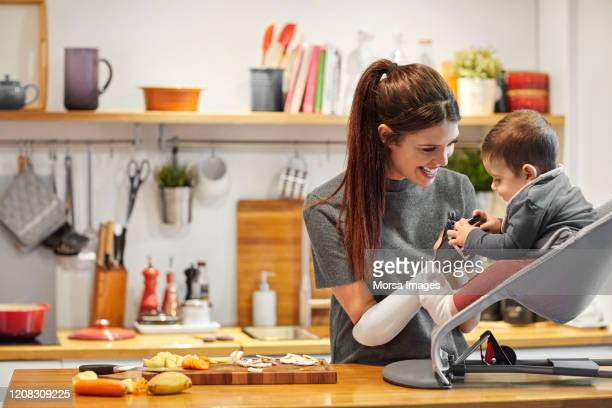 smiling mother with son in domestic kitchen - disabilitycollection foto e immagini stock
