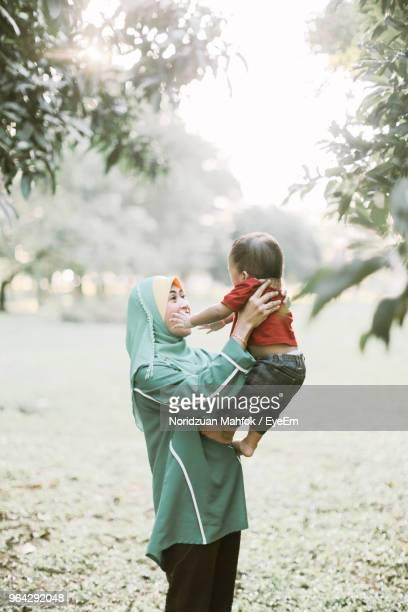 smiling mother with son playing at park - mid adult men stock pictures, royalty-free photos & images