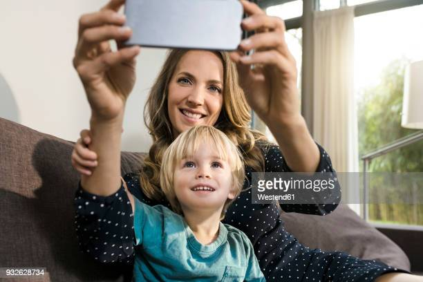 smiling mother with son taking a selfie on sofa at home - jungen fotos stock-fotos und bilder