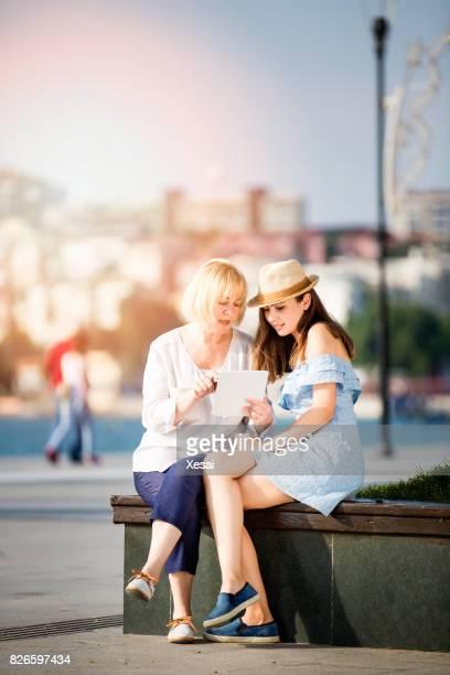 Lachende moeder met jonge dochter met digitale tablet