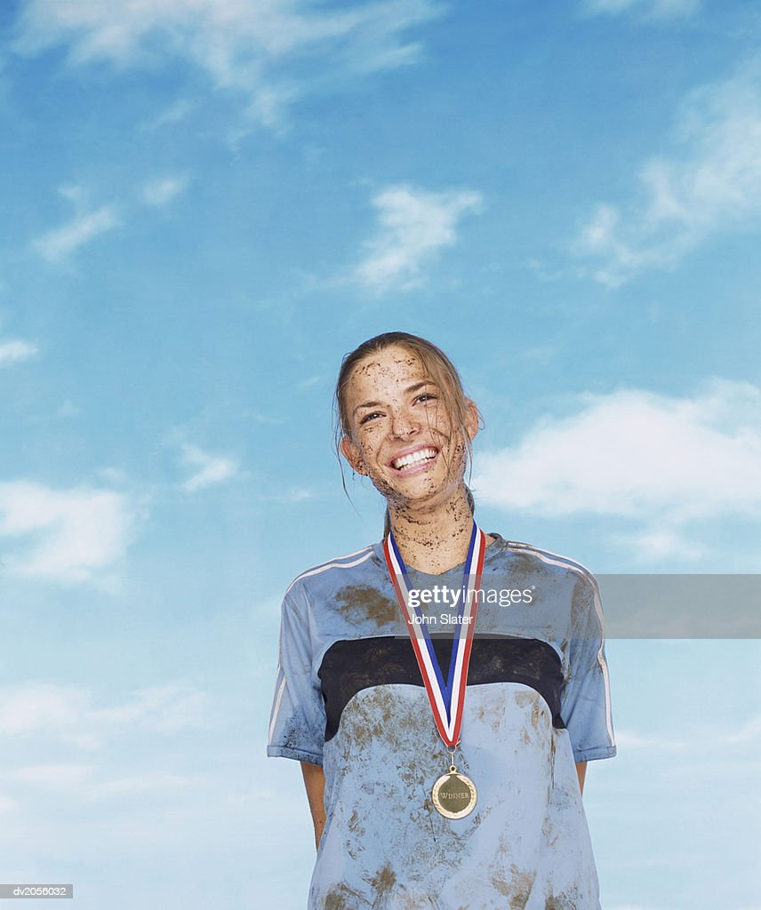 Smiling Mud Splattered Sportswoman Wearing a Gold Medal : Stock Photo