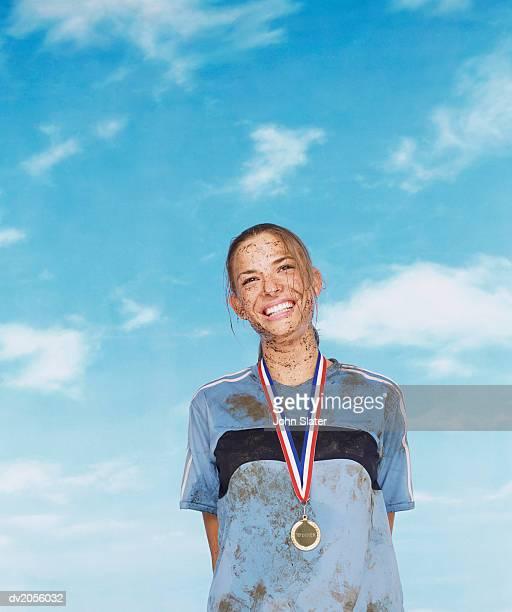 Smiling Mud Splattered Sportswoman Wearing a Gold Medal