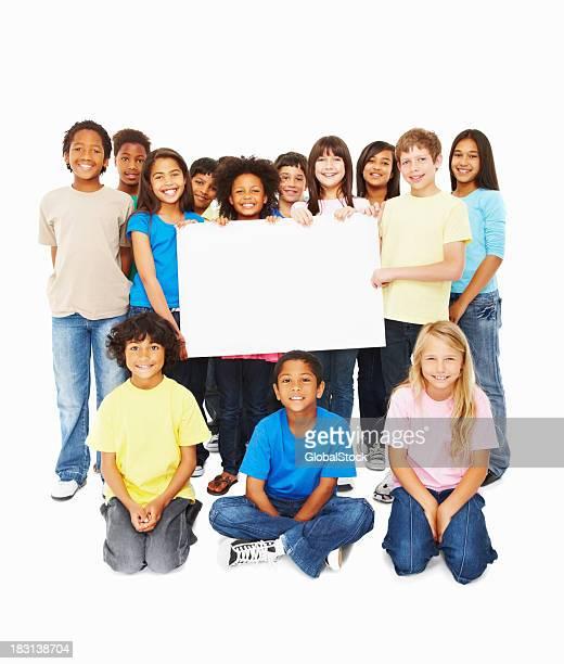 Souriant multi ethnique enfants avec un panneau d'affichage sur blanc