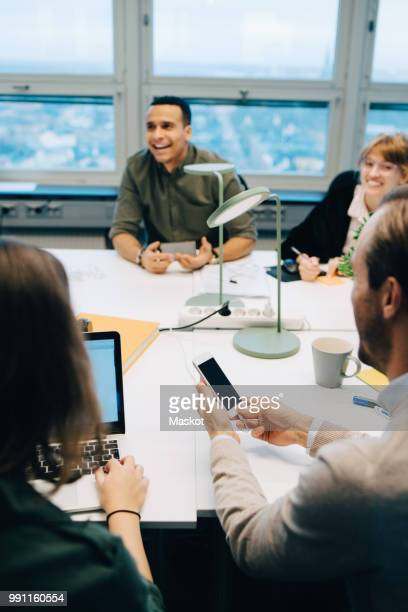 Smiling multi-ethnic business coworkers sitting at desk while discussing in board room