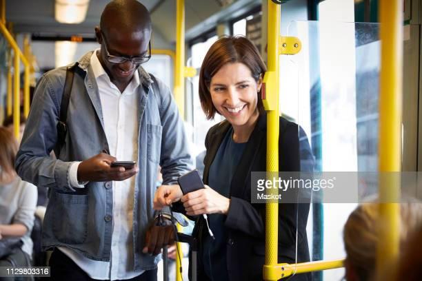 smiling multi-ethnic commuters standing in tram - incidental people stockfoto's en -beelden