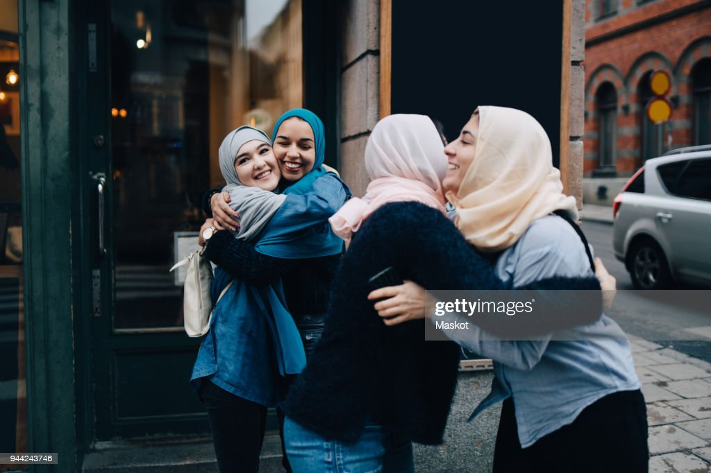 Smiling multi-ethnic female friends greeting on sidewalk in city : Stock Photo