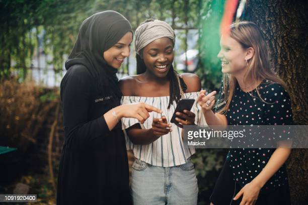 smiling multi-ethnic female friends looking at mobile phone while standing in backyard - religious veil stock pictures, royalty-free photos & images