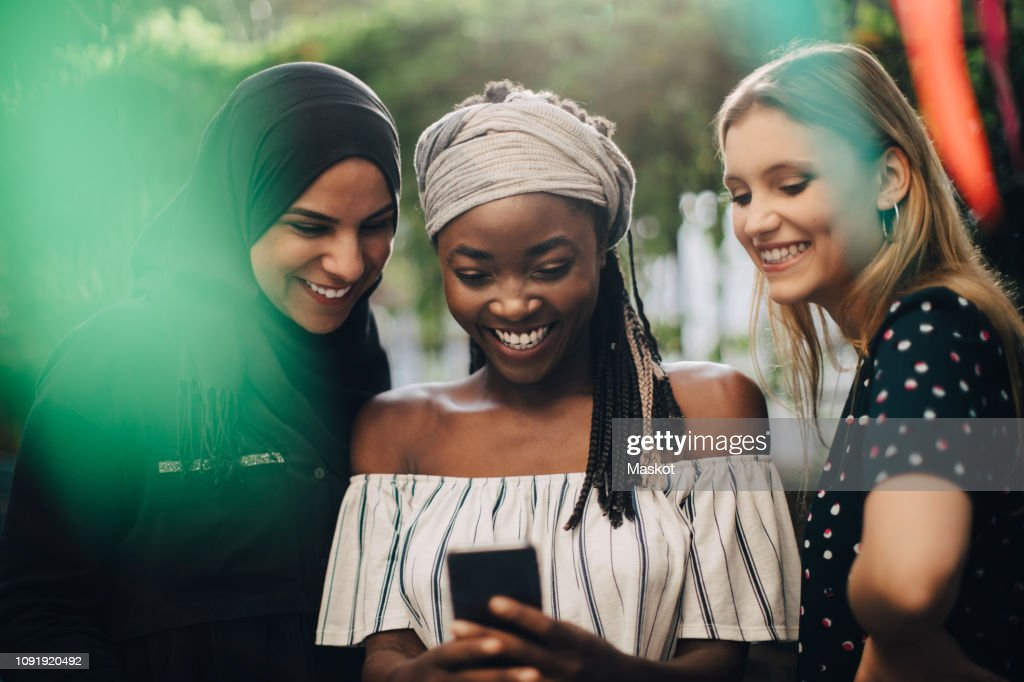 Smiling multi-ethnic female friends looking at mobile phone while standing in backyard : Stock Photo