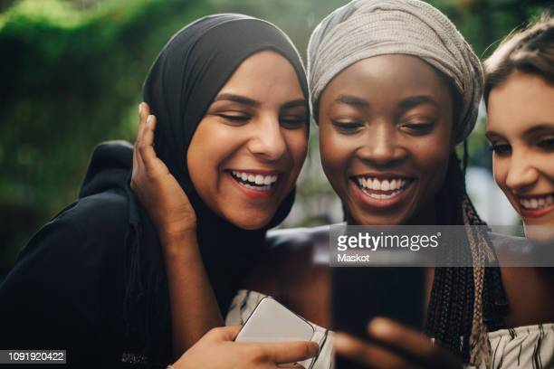 smiling multi-ethnic friends looking at mobile phone while standing in backyard - kopftuch stock-fotos und bilder