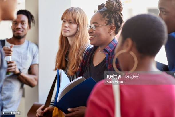 smiling multi-ethnic friends standing in corridor - community college stock pictures, royalty-free photos & images
