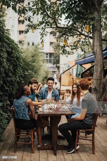Smiling multi-ethnic group of people having fun at the pub