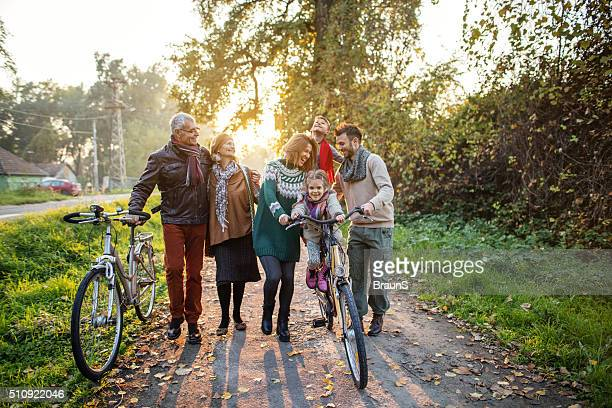Smiling multi-generation family on bicycles in the park.