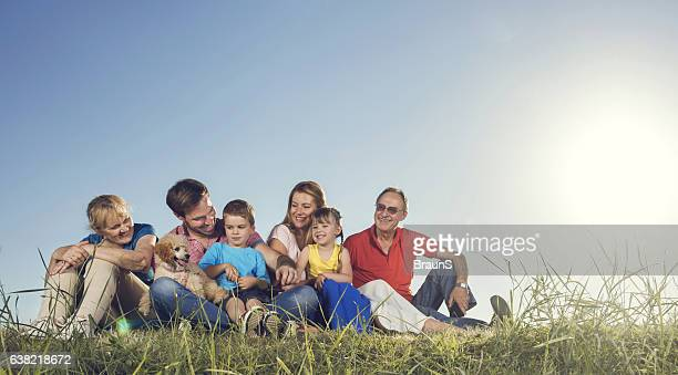 Smiling multi-generation family relaxing with their dog in a meadow.