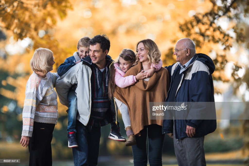 Smiling multi-generation family talking during autumn day in nature. : Stock Photo