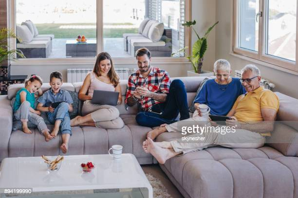 smiling multi-generation family using wireless technology while relaxing in the living room. - gear stock pictures, royalty-free photos & images