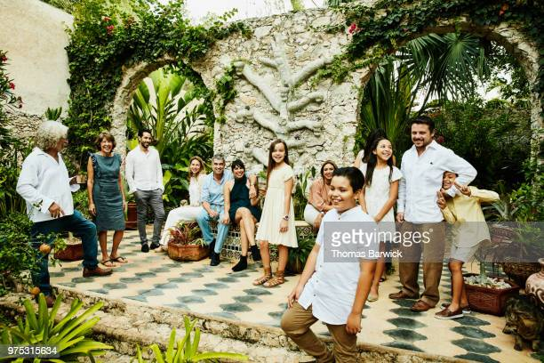 Smiling multigenerational family gathered for portrait in backyard courtyard garden