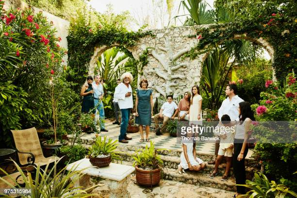 Smiling multigenerational family sharing drinks in backyard garden during dinner party