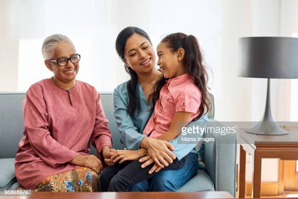 smiling multi-generational family sitting at home - three people stock pictures, royalty-free photos & images