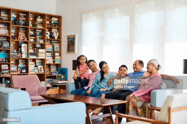 smiling multi-generational family sitting on sofa - malay stock photos and pictures