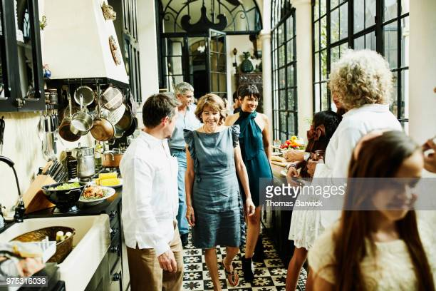 Smiling multigenerational family walking through kitchen during family dinner party